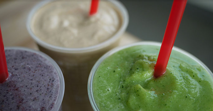 Red straws sit in the open tops of three smoothies, one purple, one cream-colored and one green.